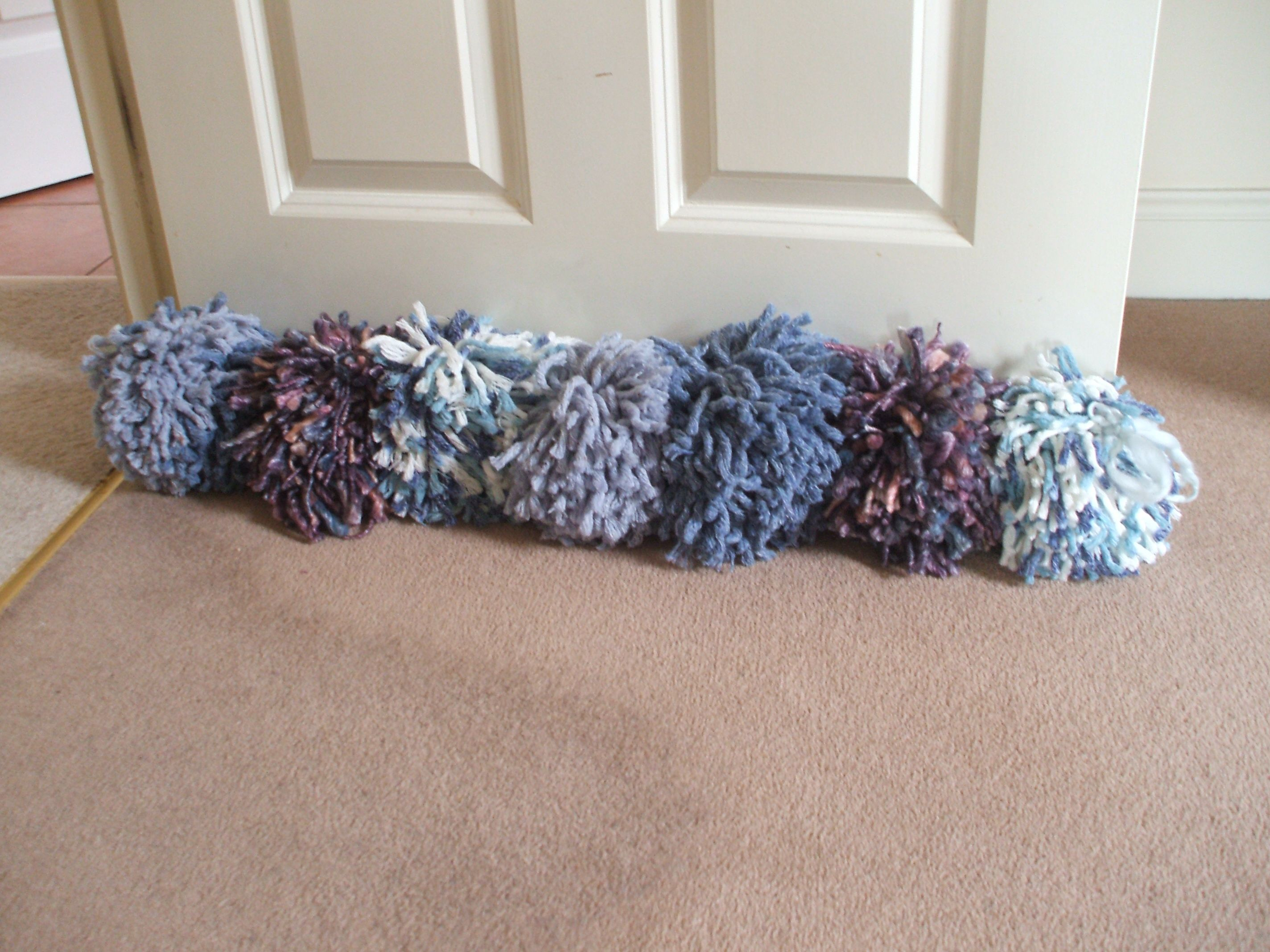 389c0932601 Quirky draught excluder made from 7 large pom poms. Strung together with  wool ribbon.