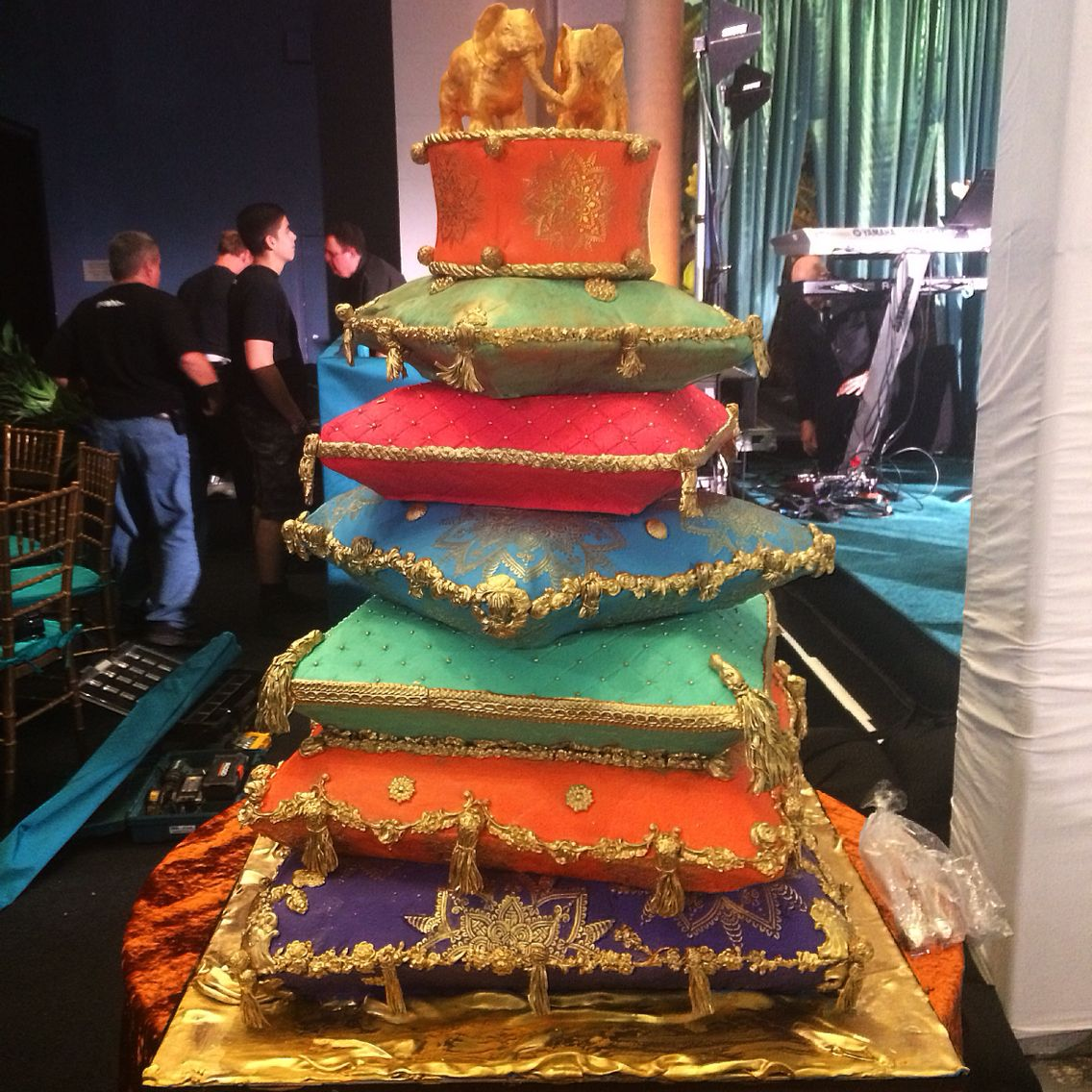 Stacked pillow jewel tone wedding cake Indian theme with gold elephants on top. Pillows have decor with NY buildings in it