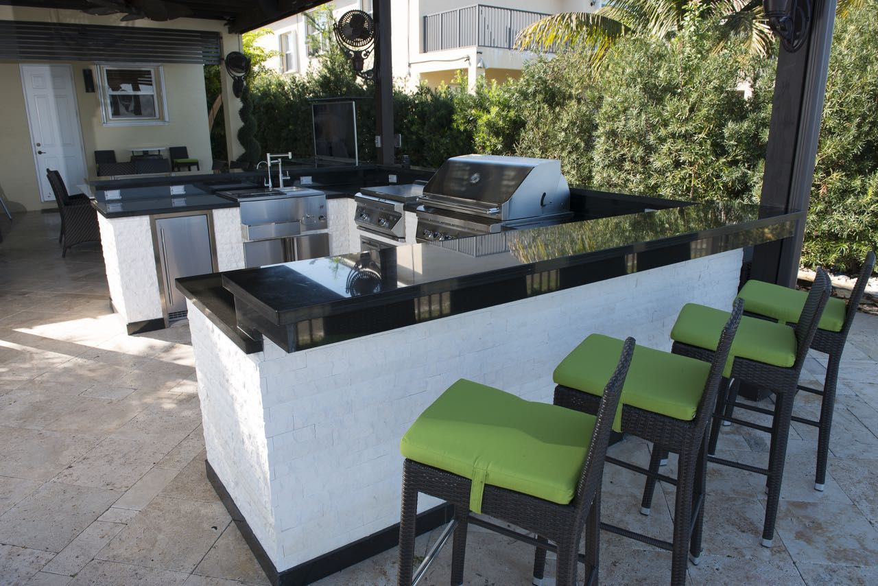 Whitewashed stone U-shaped outdoor kitchen with black granite ...