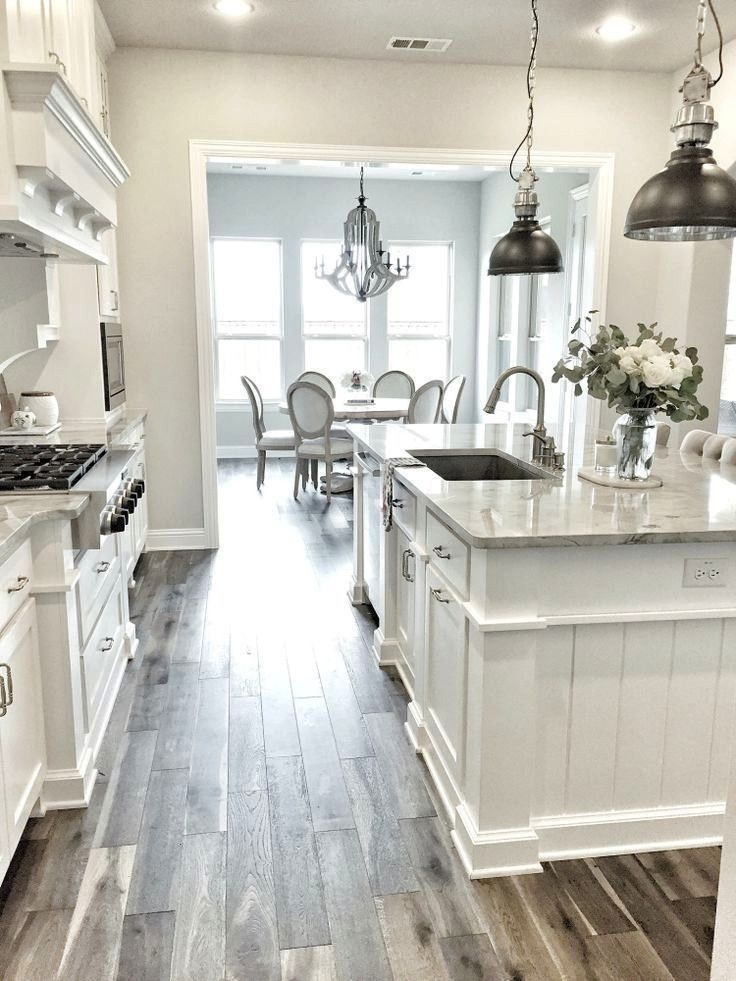 obsessed with this white kitchen The pendant lights and wood tile floor makes for a really gorgeous roomIm obsessed with this white kitchen The pendant lights and wood ti...