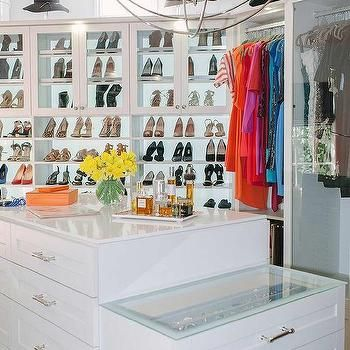 White Walk In Closet With Orange Accents Boasts An Angled Drop Down Center Island Fitted Polished Nickel Pulls And A Glass Top Accented