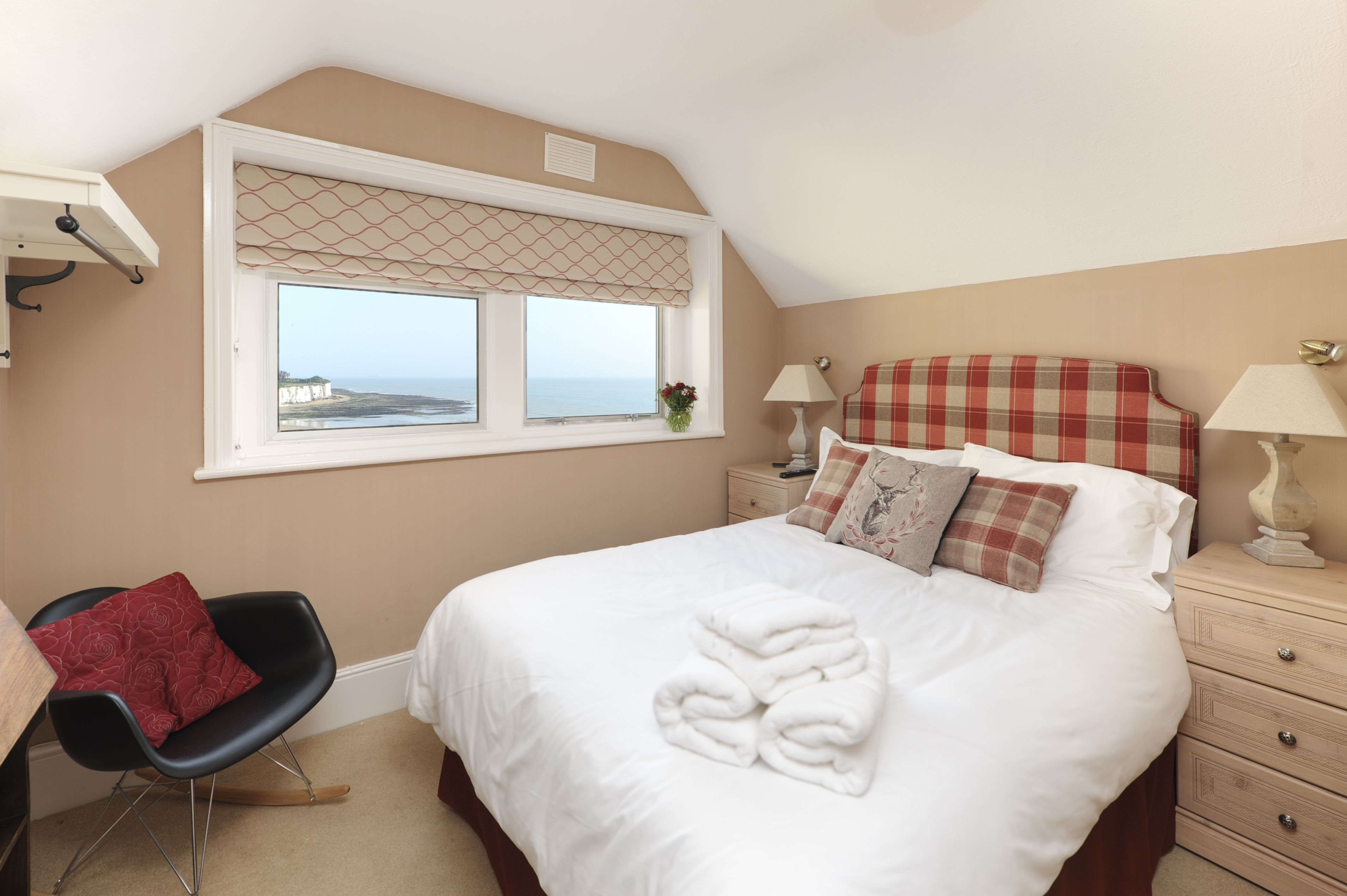Bed with window behind it  room with view of sea and cliffs to our left prior to our