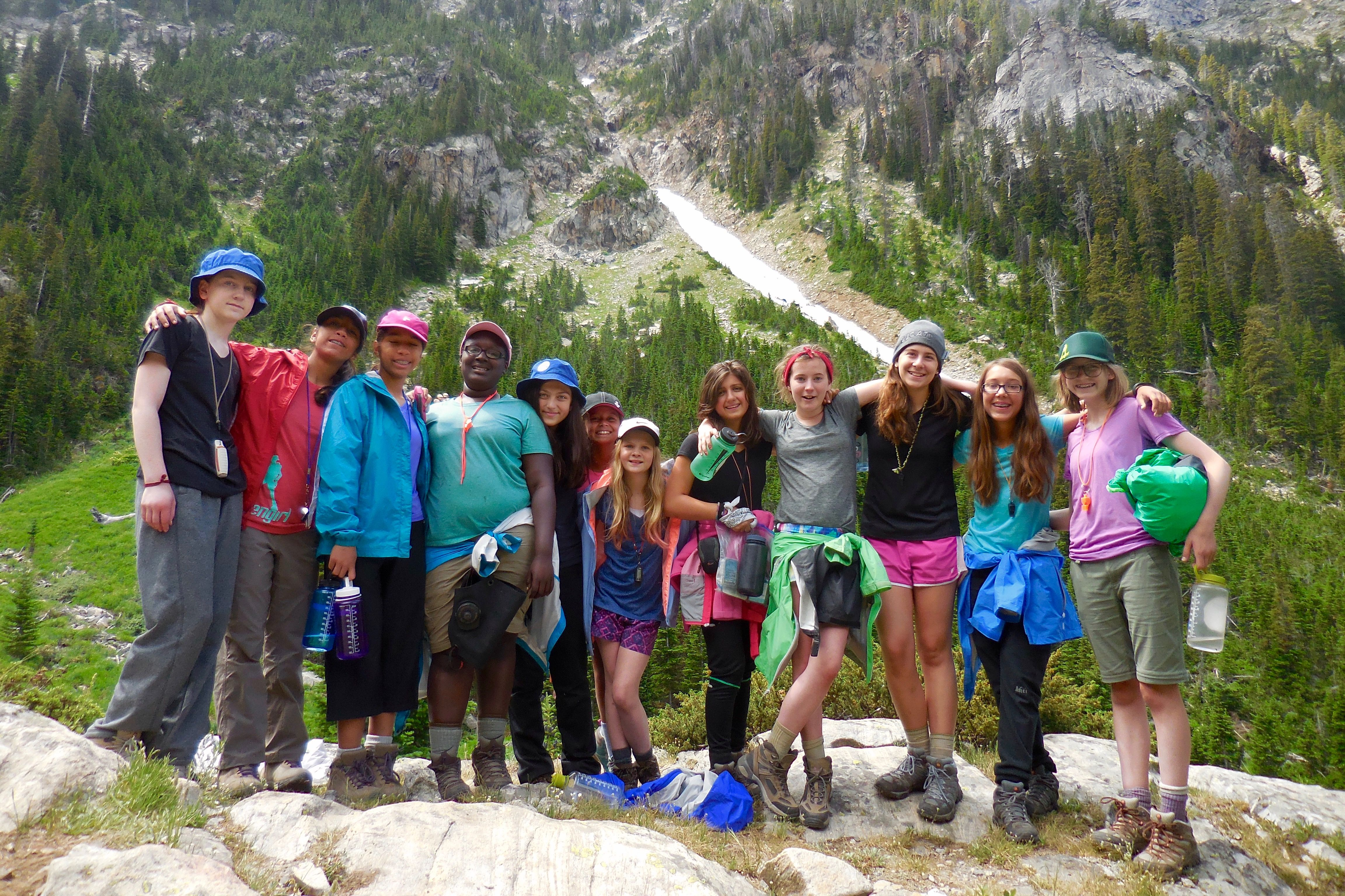 Girls summer camp group backpacking and hiking in the