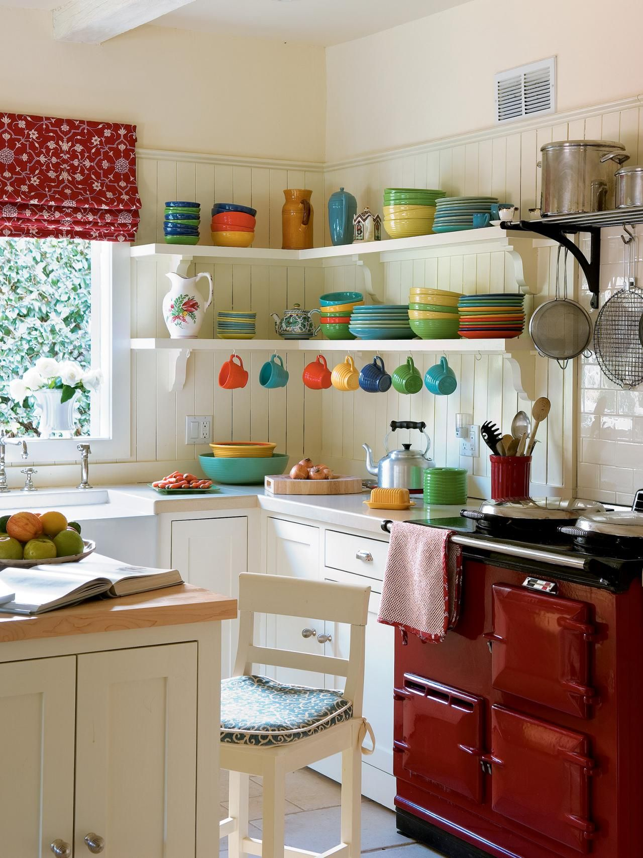 Colorful Fiestaware adds pops of color to this white country kitchen. A red Roman shade matches a red stove. There's a cozy bit of clutter to make you feel at home. #kitchenremodelsmall