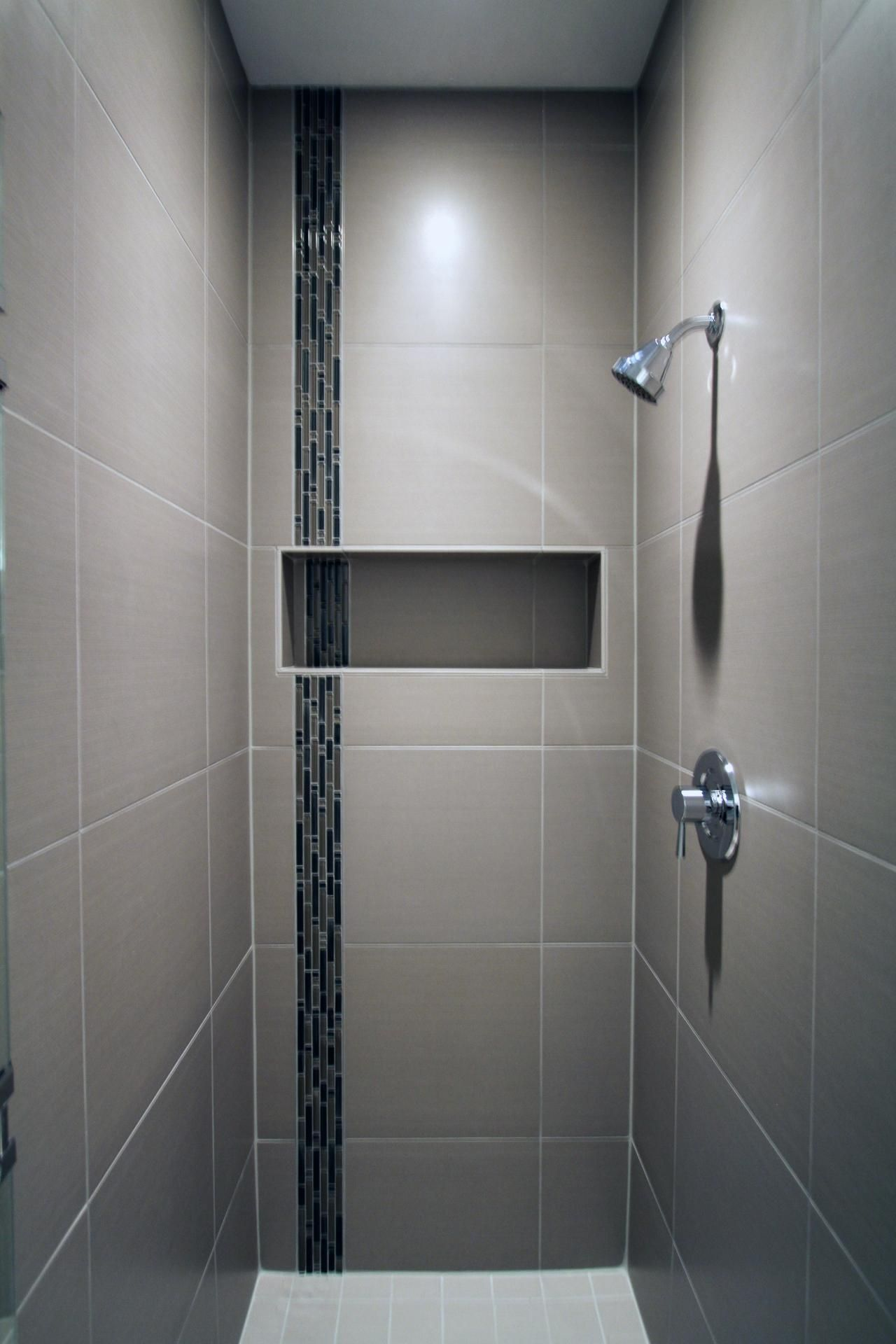 The Porcelain Tile Of This Sleek Shower Surrounds A Glass Accent Tile Stripe And Built In Niche