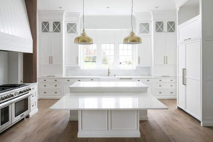 White Kitchen With A Drop Down Dining Table Built Into A Dining Island Featuring Shiny Brass Lanterns Kitchen Island With Seating Modern Kitchen White Kitchen