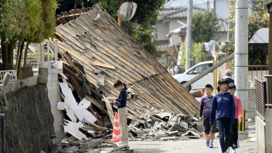 Children walk past a house collapsed by a magnitude-6.5 earthquake in Mashiki, Kumamoto prefecture, southern Japan, Friday, April 15, 2016. The powerful earthquake struck Thursday night, knocking down houses and buckling roads. (Koji Harada/Kyodo News via AP) JAPAN OUT, MANDATORY CREDIT