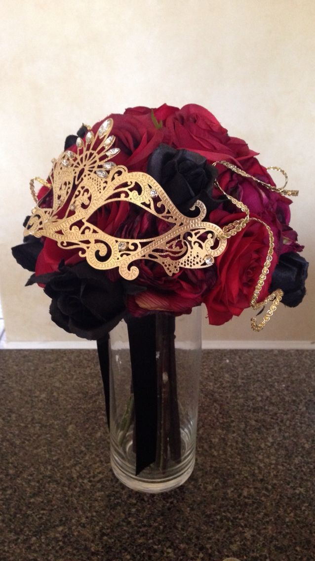 A Clear Vase With Rose Bouquet Topped An Elegant Gold Masquerade Mask Incorporates The Theme Colors And Focus Point Of