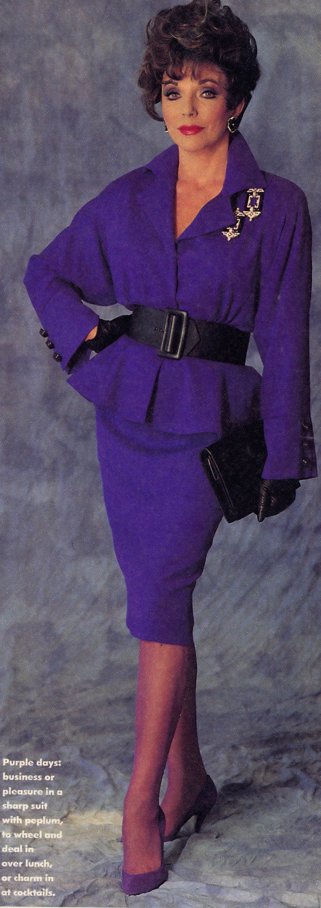 Joan Collins matches her purple suit with black handbag on Dynasty the Reunion.