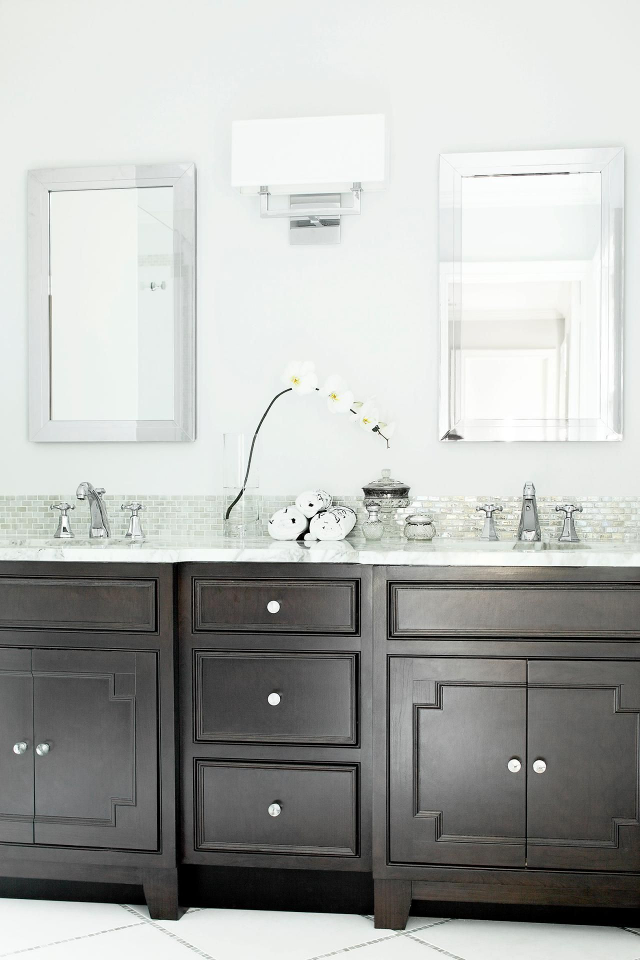 A dark wood vanity creates contrast against bright white walls in
