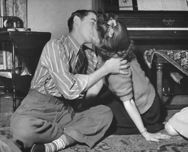 Teen Fads, 1942 - teens kissing during a game of spin the bottle at a party