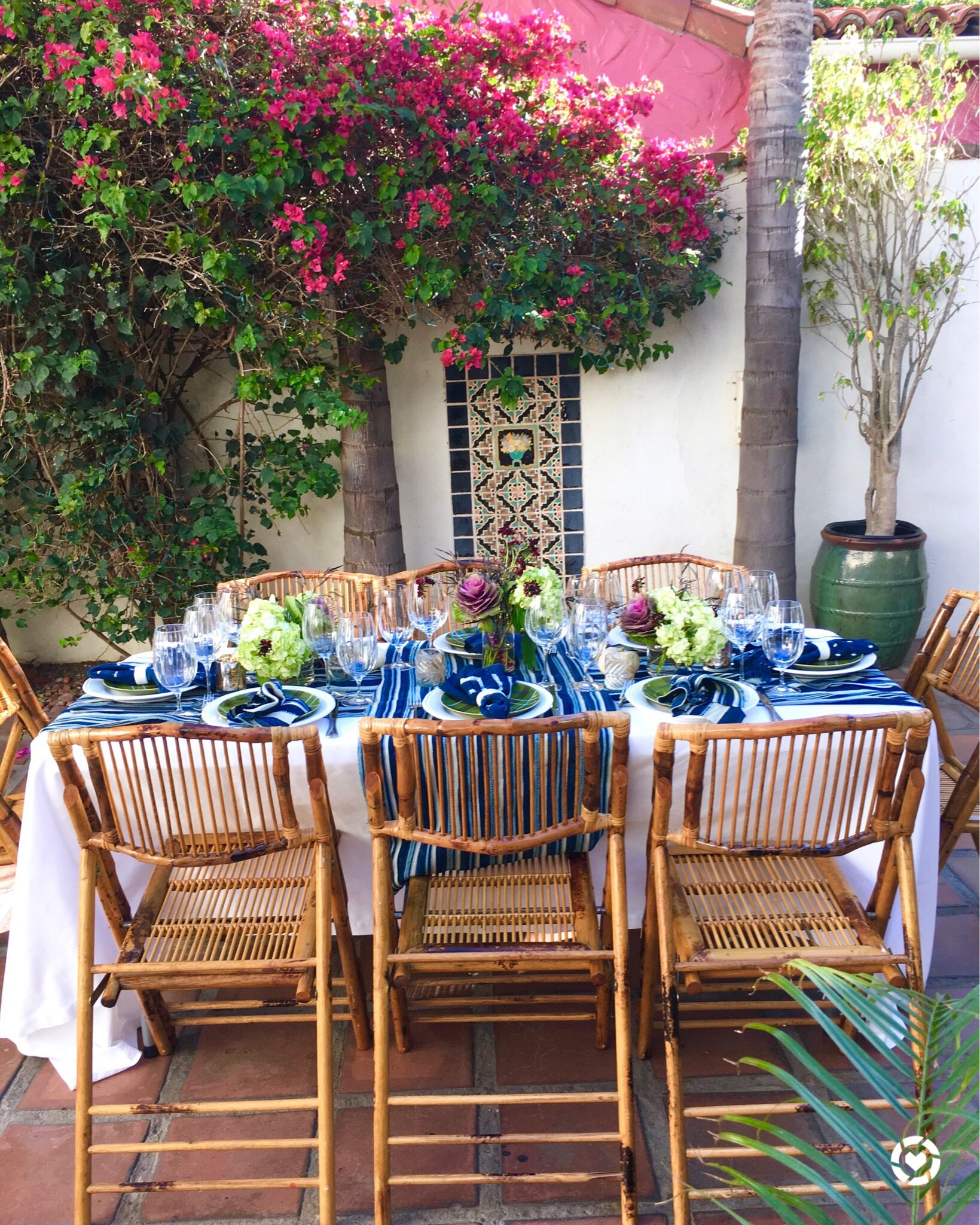 Outdoor dining table with bamboo chairs and indigo napkins and table runner i used ornamental cabbage and hydrangea for my flower arrangements