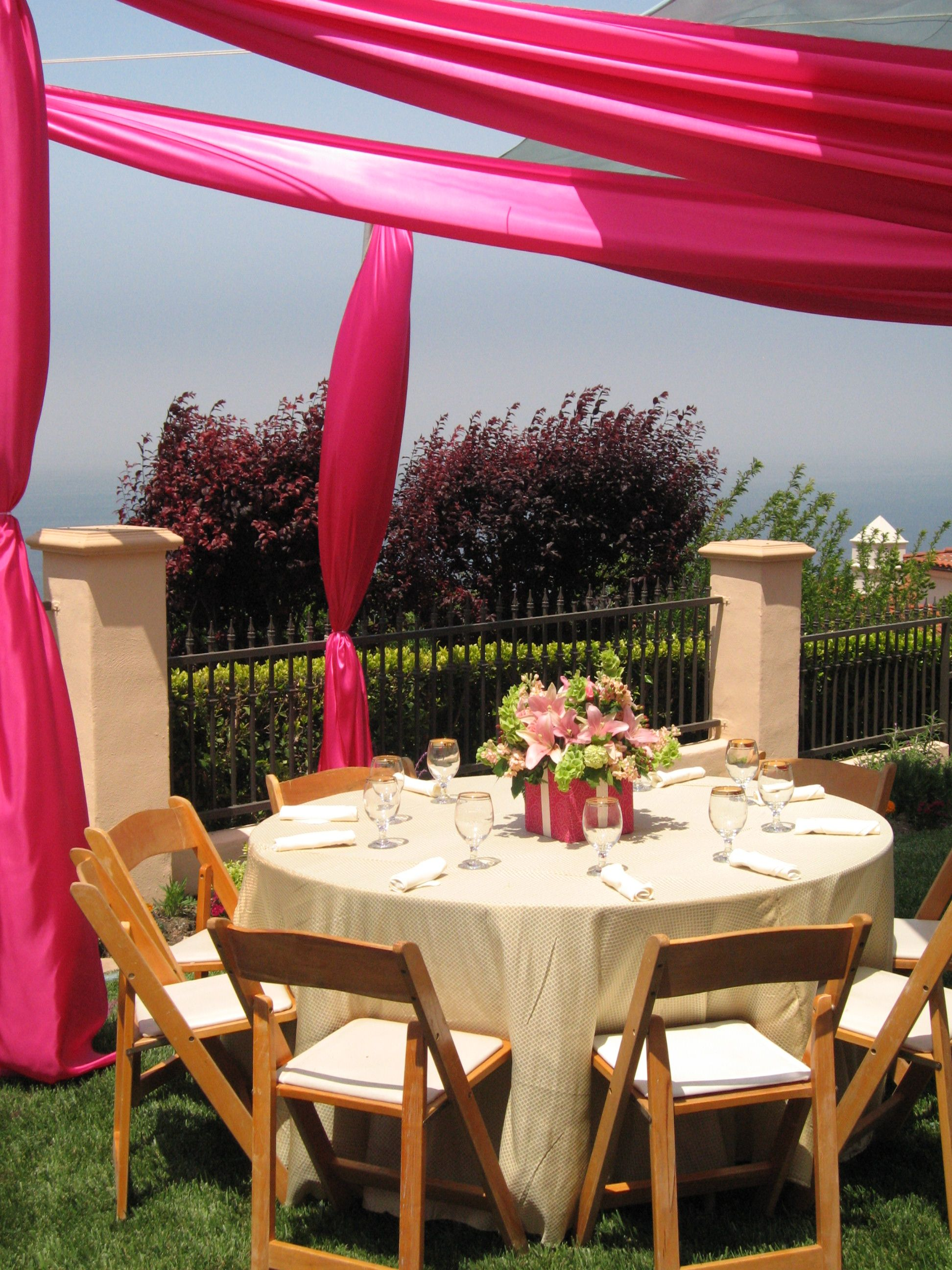 Natural wood padded folding chairs and custom pink fabric tent