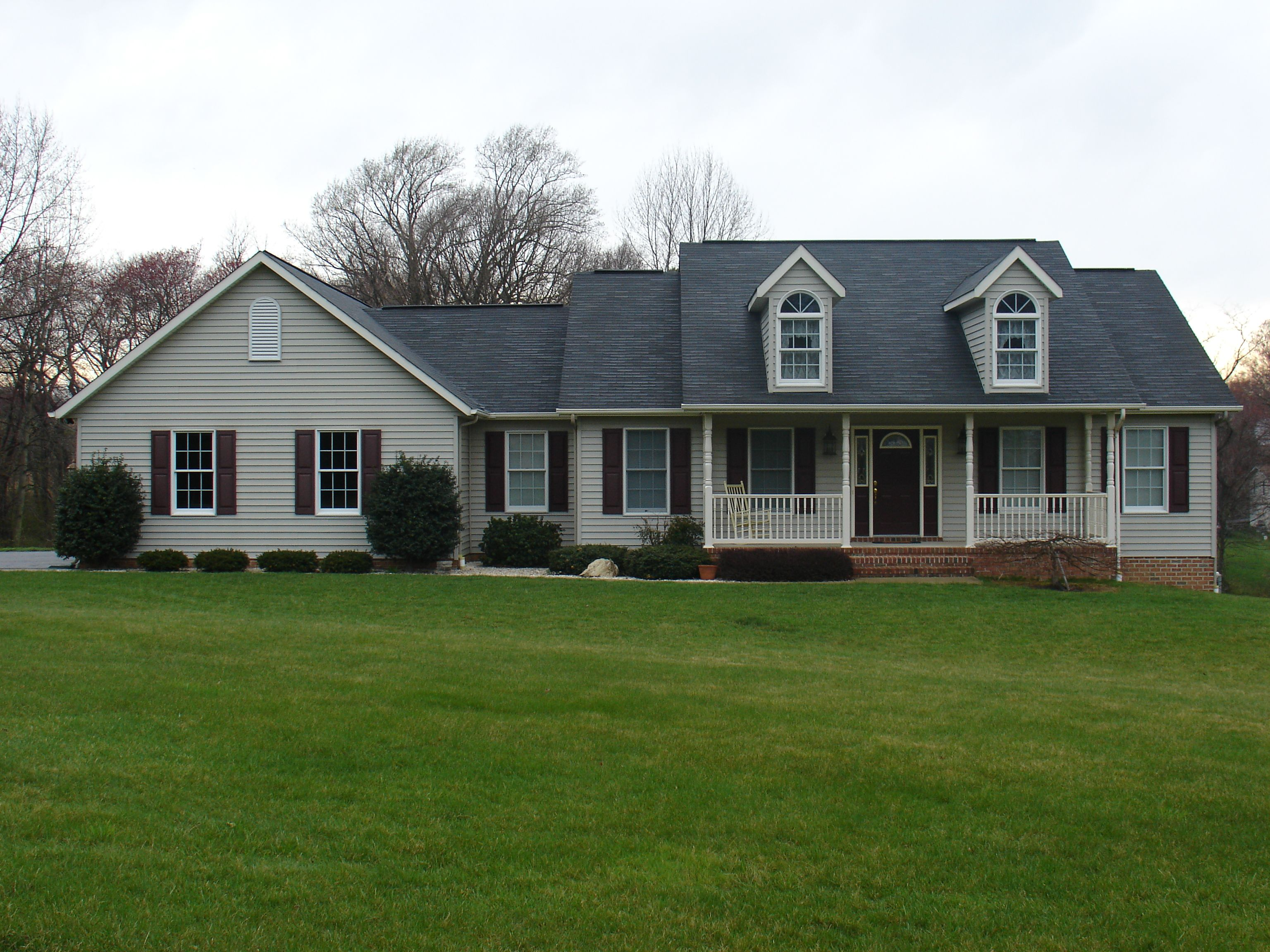 Front view custom rancher with two dormers to look like a for Cape cod dormer