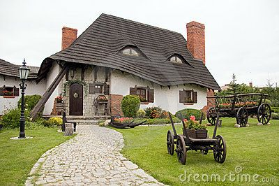 Old-fashioned polish house with farm carriage flowerpot ...