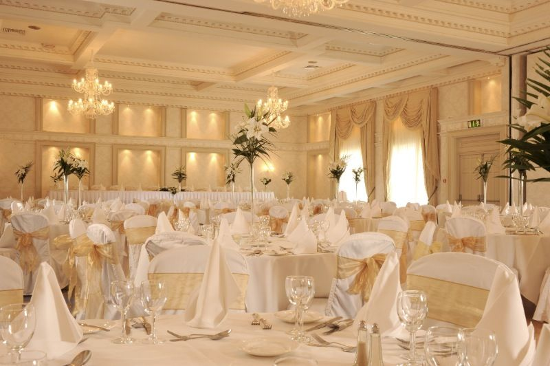 A Reception Hall That Is Classical White With Golden Accents Simple Lily Arrangements Standing Tall And Proud Throughout The Ballroom