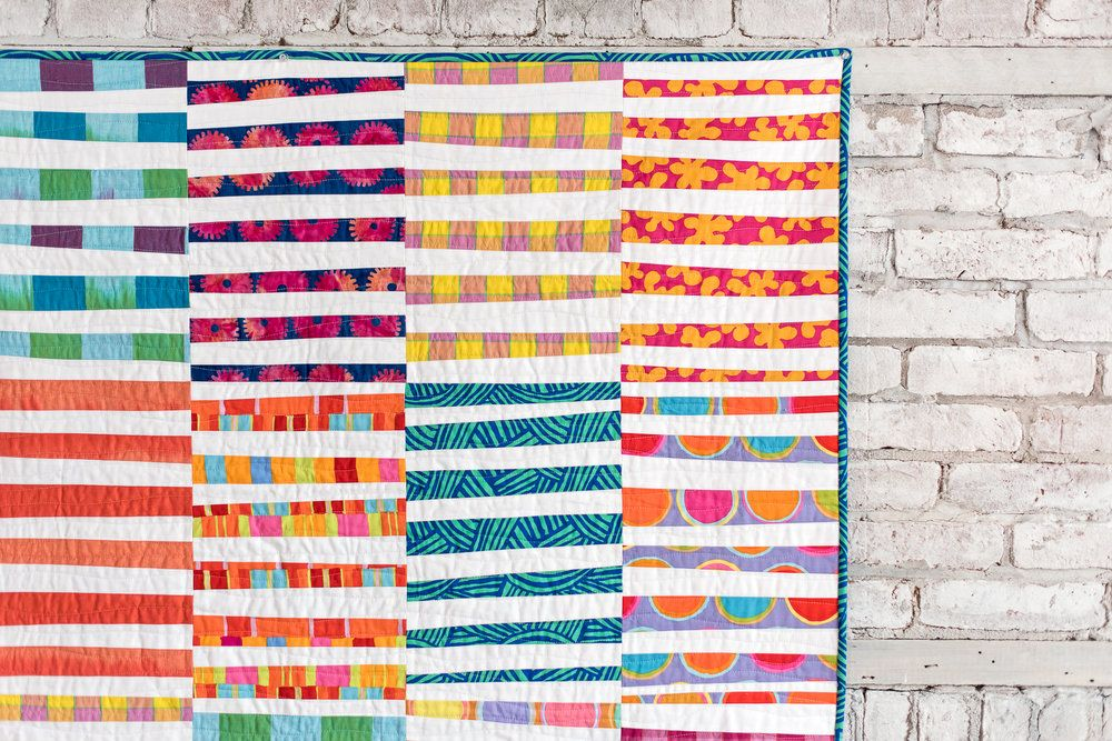 Today is my stop on the Kaffe Fassett Artisan Blog Tour! I'm excited to  share this quilt I made with Kaffe's latest fabric collection for  Freespirit Fabrics, called Artisan. I used a mix of fabrics from both  colorways, Sunny and Blue. I also used a mix of fabric types, including  wovens, batiks and quilting cottons, all of which are included in the  Artisan Collection.  I was completely inspired by a quilt made recently by my friend Nancy of  Owen's Olivia, and knew a similar block design…