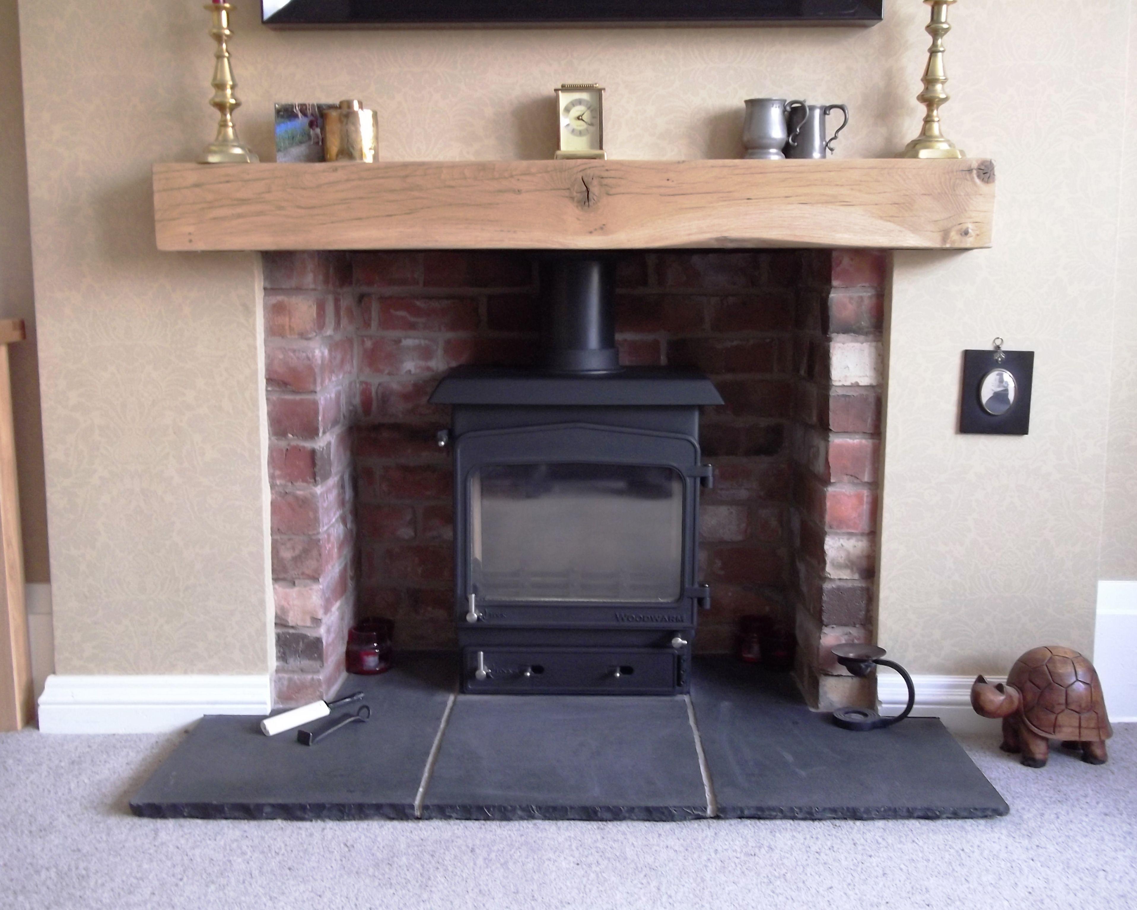 Brick fireplace, oak beam with black Indian stone hearth, Woodwarm ...