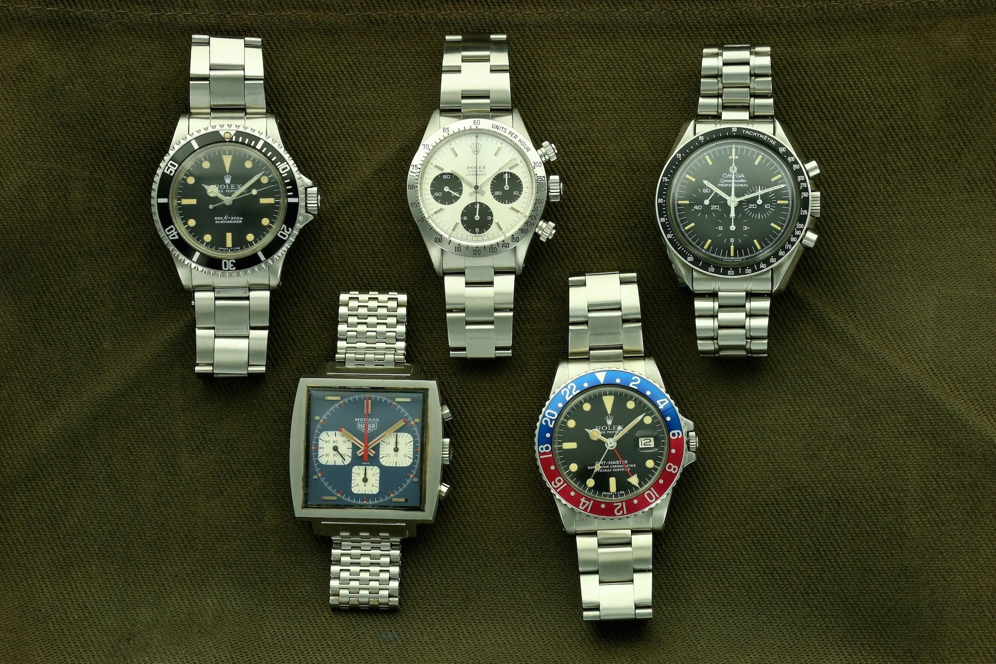 Five vintage sports watches; Rolex Submariner, Heuer Monaco, Rolex Daytona, Rolex GMT-Master, Omega Speedmaster