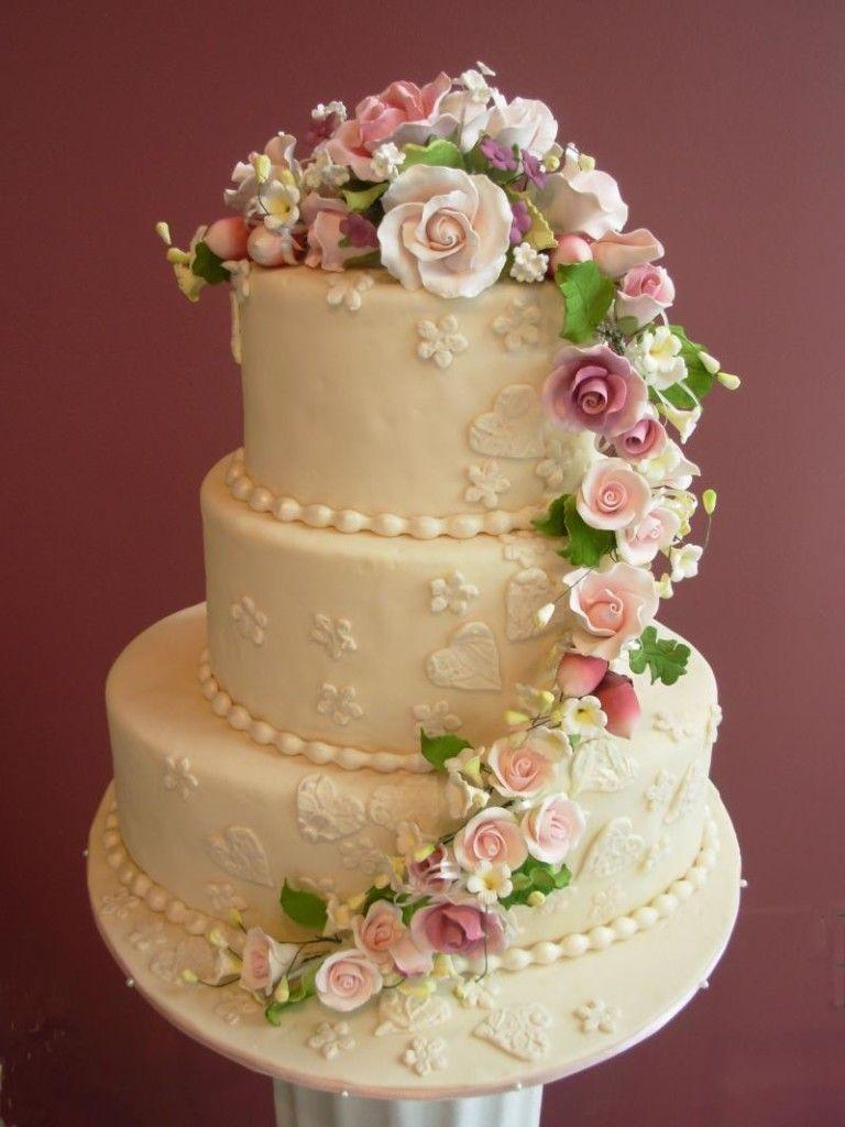 Cascading flowers on threetier wedding cake pretty cakes