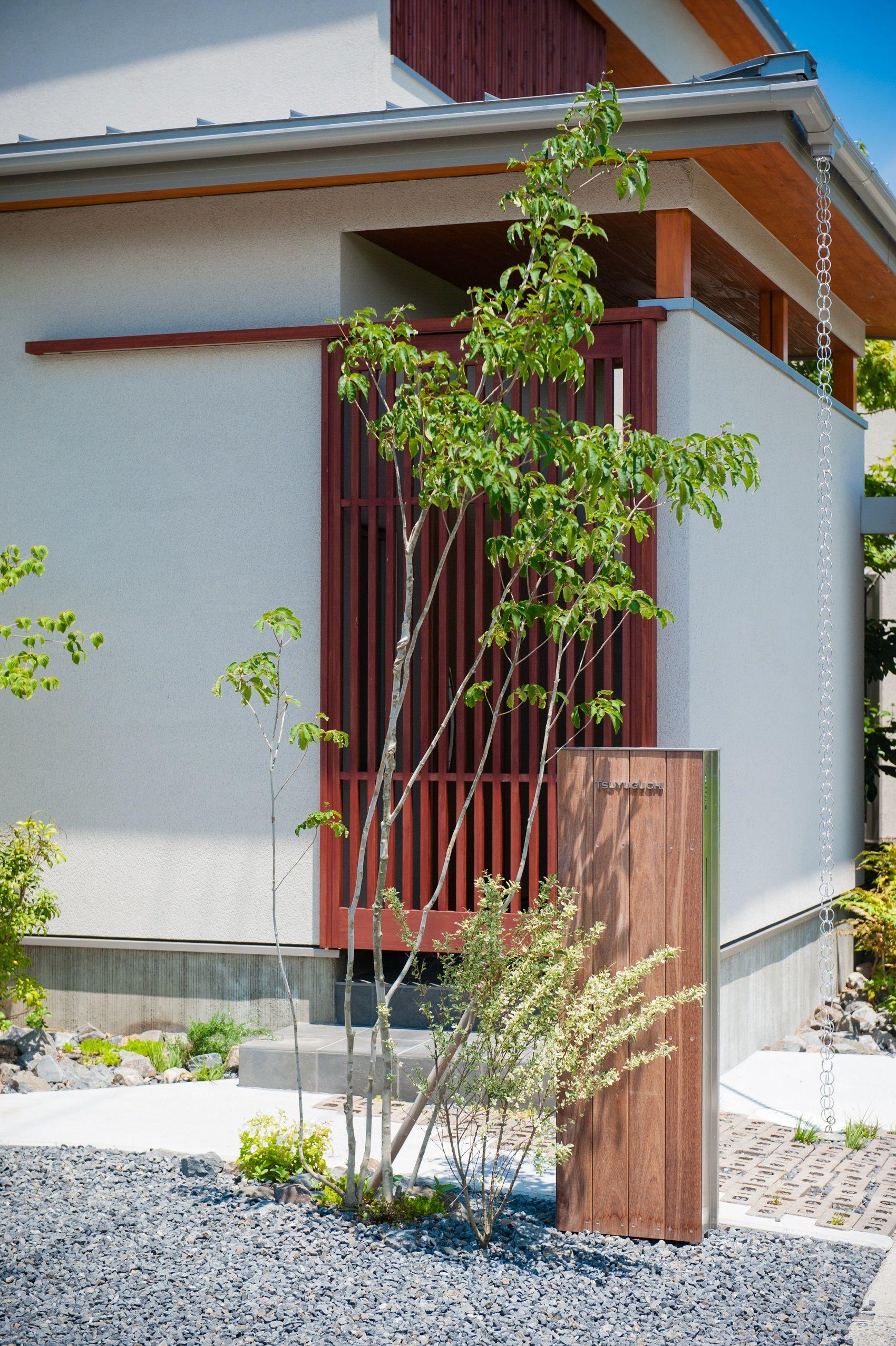 外壁と植栽 白の塗壁に赤みがかった木の格子が差し色を入れました