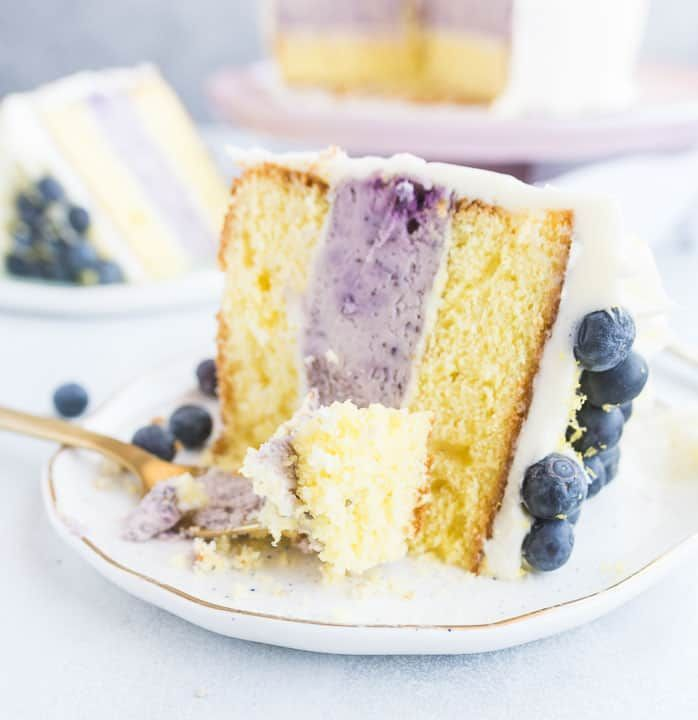 Lemon Blueberry Cheesecake Layer Cake #lemonblueberrycheesecake This lemon blueberry cheesecake layer cake features a layer of blueberry cheesecake between two layers of lemon cake, all topped with cream cheese frosting. It's a perfect dessert for Easter, Mother's Day, or any day this spring! recipe and how-to via itsybitsykitchen.com #Easter #dessert #mothersday #recipe #cake #lemonblueberrycheesecake