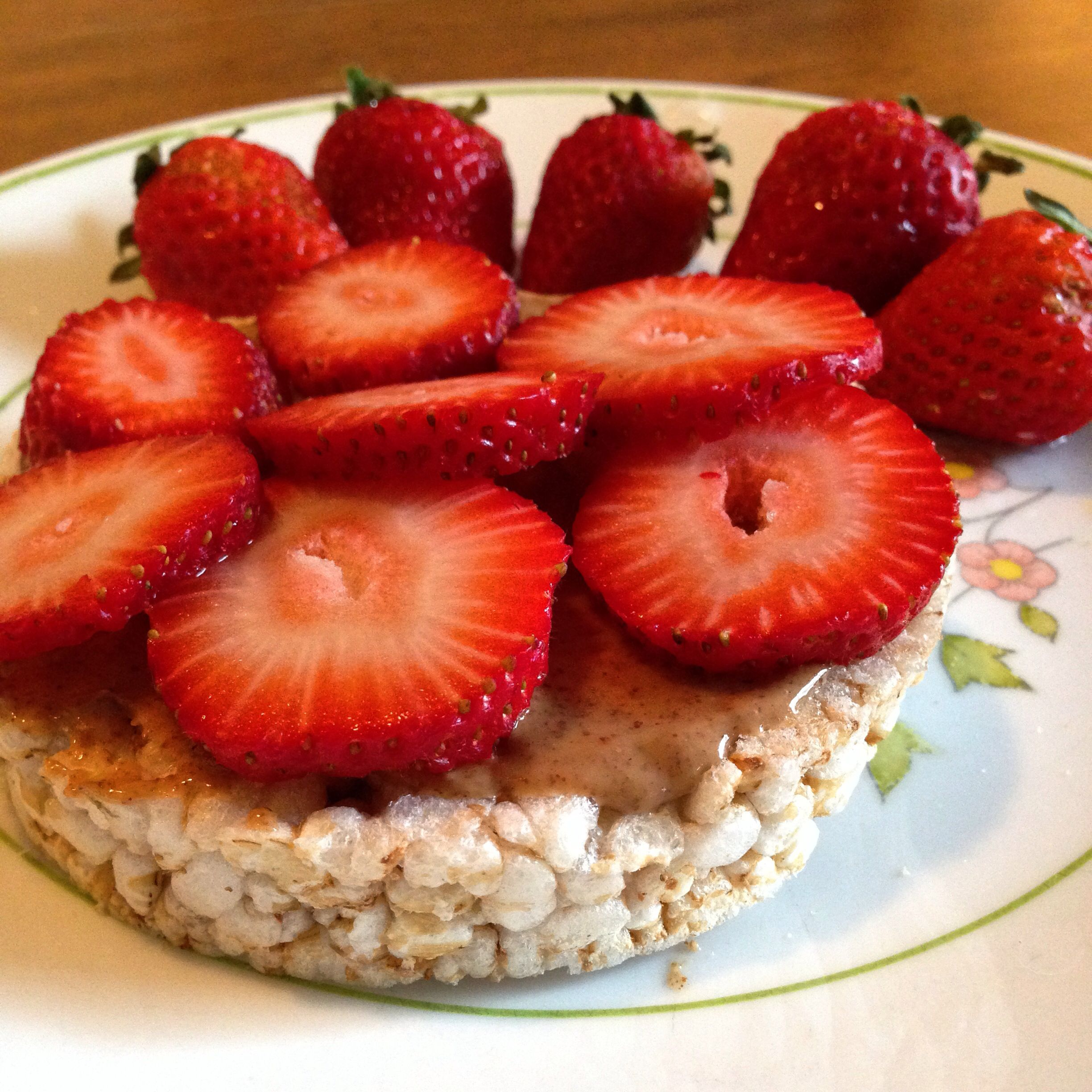 Organic rice cake topped with almond butter and slivered strawberries. Perfect afternoon snack!!