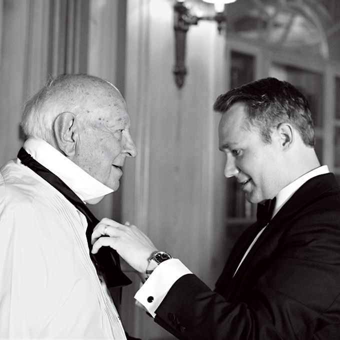 A groomsman helping the groom's grandfather, the best man, with his tie. Photo by Patricia Lyons.