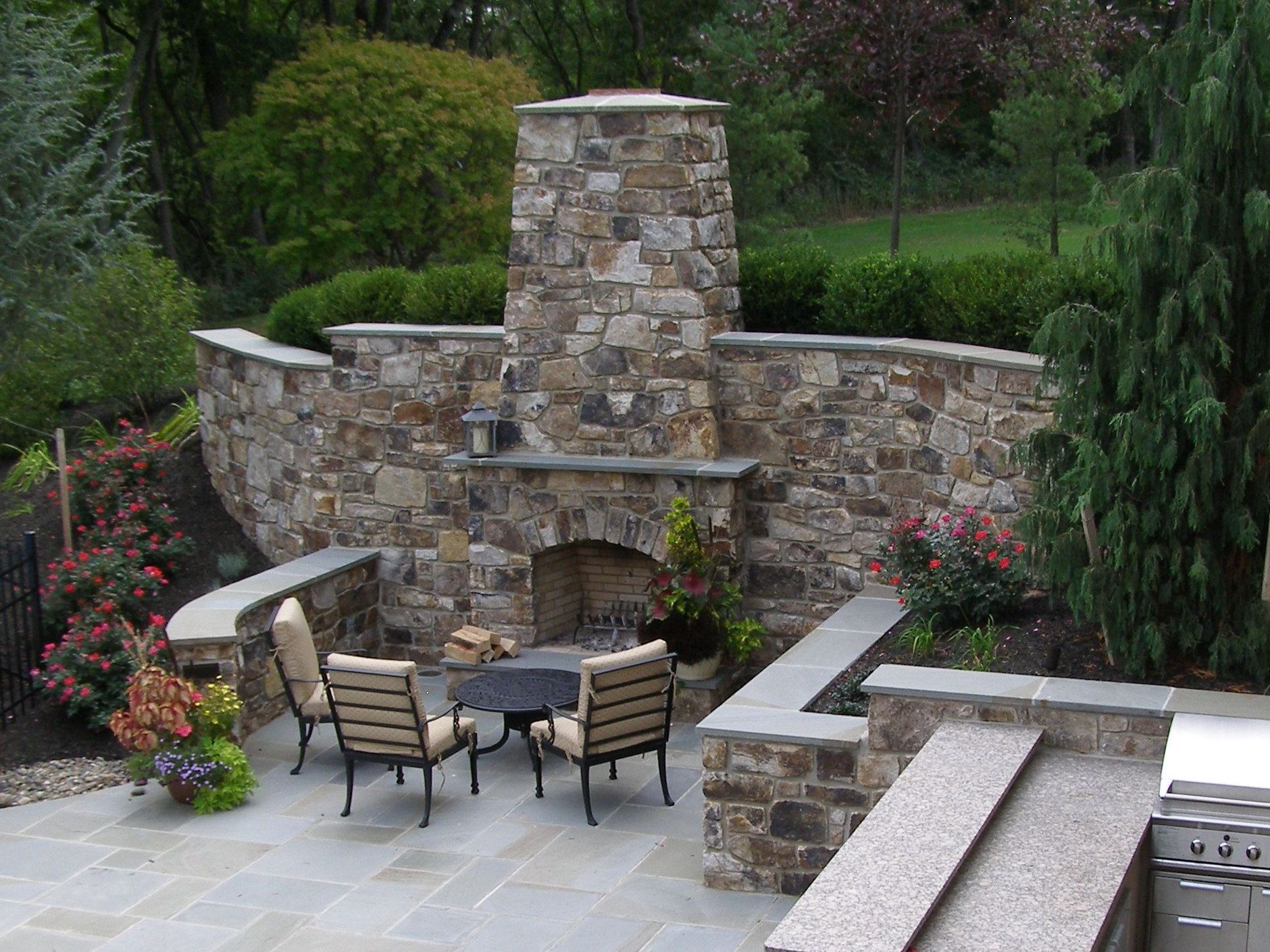 outdoor fireplace incorporated into high stone wall with boxwood