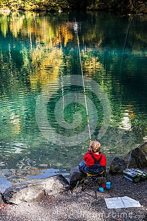 Blausee, Switzerland.>A boy concentrating to catch a fish with his fishing pole. Every October, Blausee welcomed people to fish for trouts.