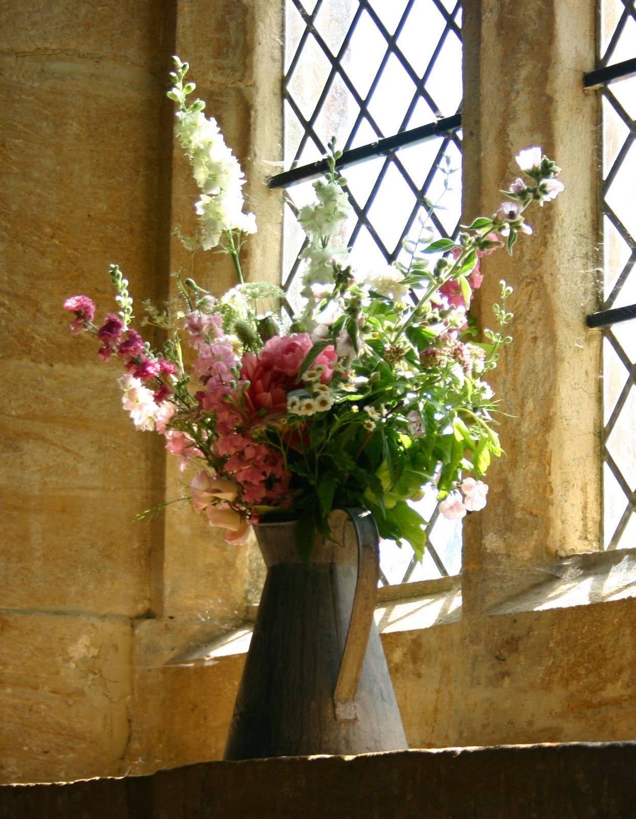Vintage jug of flowers as a window dressing for the church ...