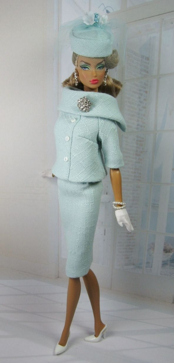Silkstone Barbie dressed in a divine two piece Chanel inspired suit. The suit is made from a pale turquoise blue material. With a lovely attached brooch and matching hat.