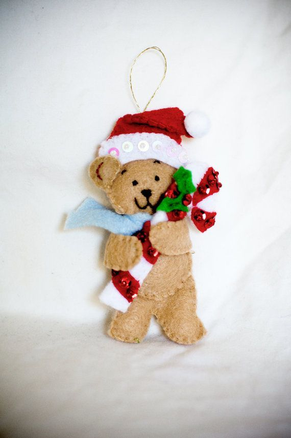 Photo of Cute Little Christmas Felt Teddy Bear with Santa Hat and Scarf, Holding Holly Decorated Candy…