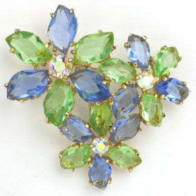 Faceted pale sapphire and peridot glass stones form the petals of three flowers with AB centers, in this lovely 1950s brooch by Elsa Schiaparelli.