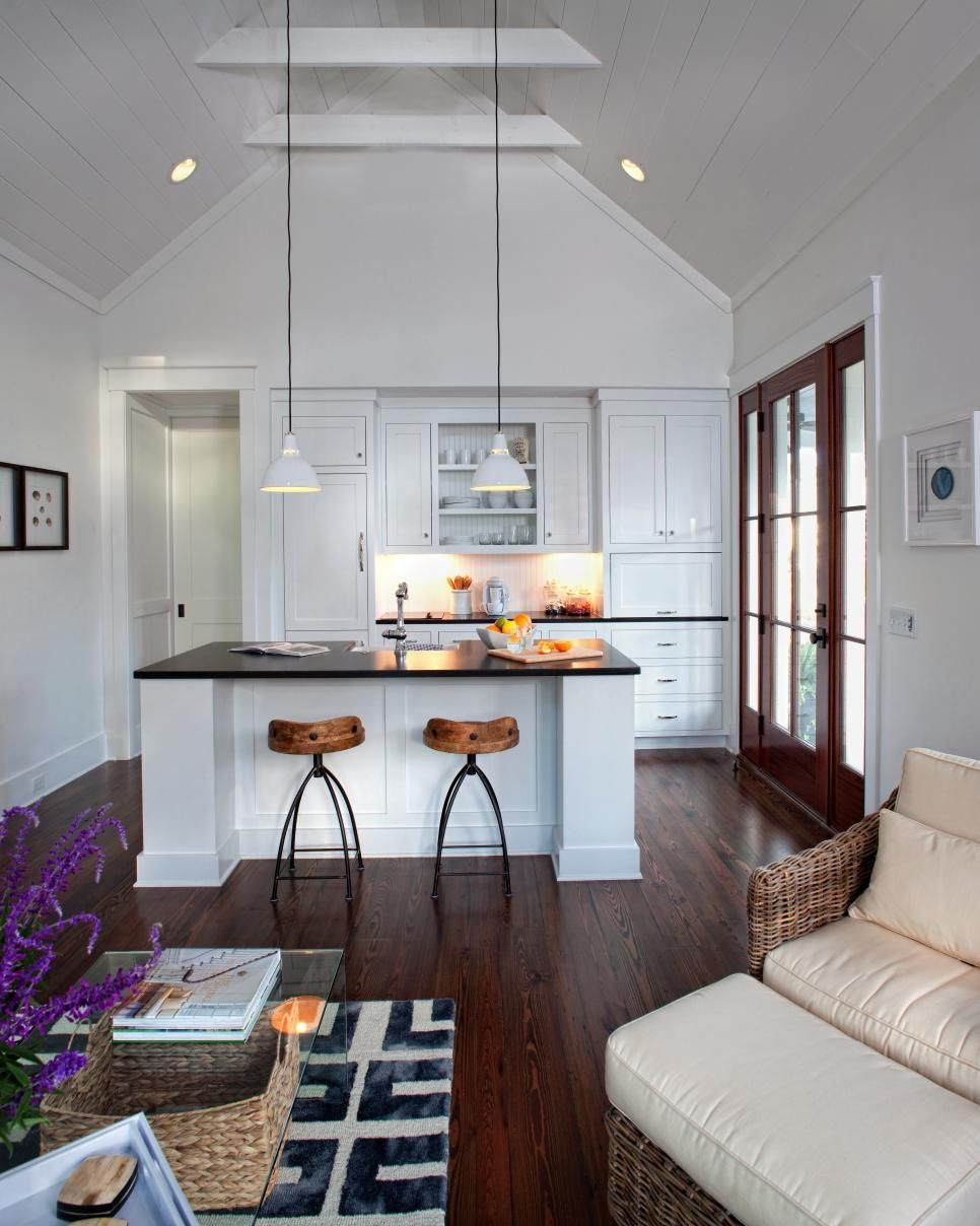 A vaulted ceiling clean white walls and a front door with large