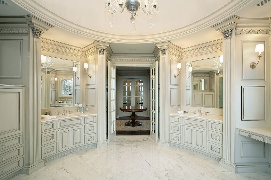 Stately, circular bathroom features a pair of curved vanities and white  cabinetry throughout, with a carved ceiling holding chandelier at center.