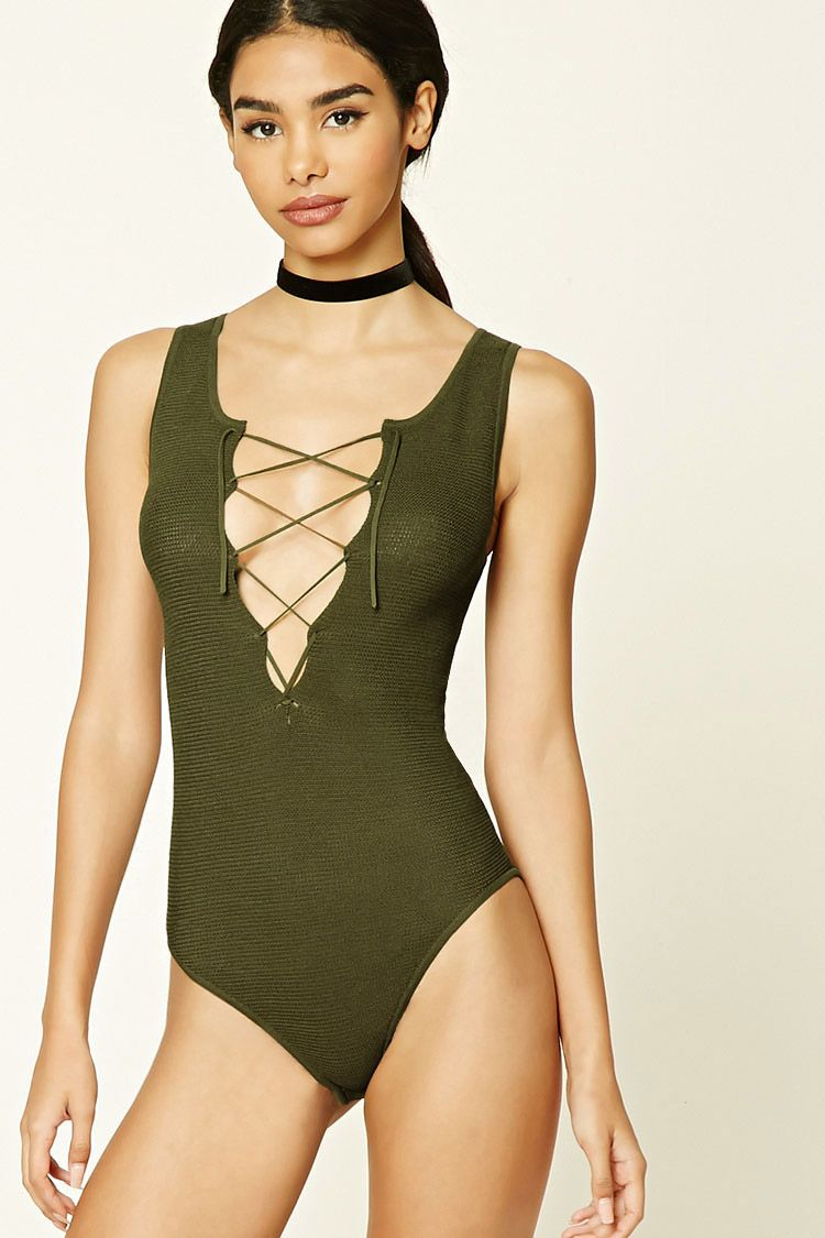 A ribbed knit bodysuit featuring a raw-cut plunging neckline, self-tie lace-up front, sleeveless cut, scoop back, and a snap-button closure.