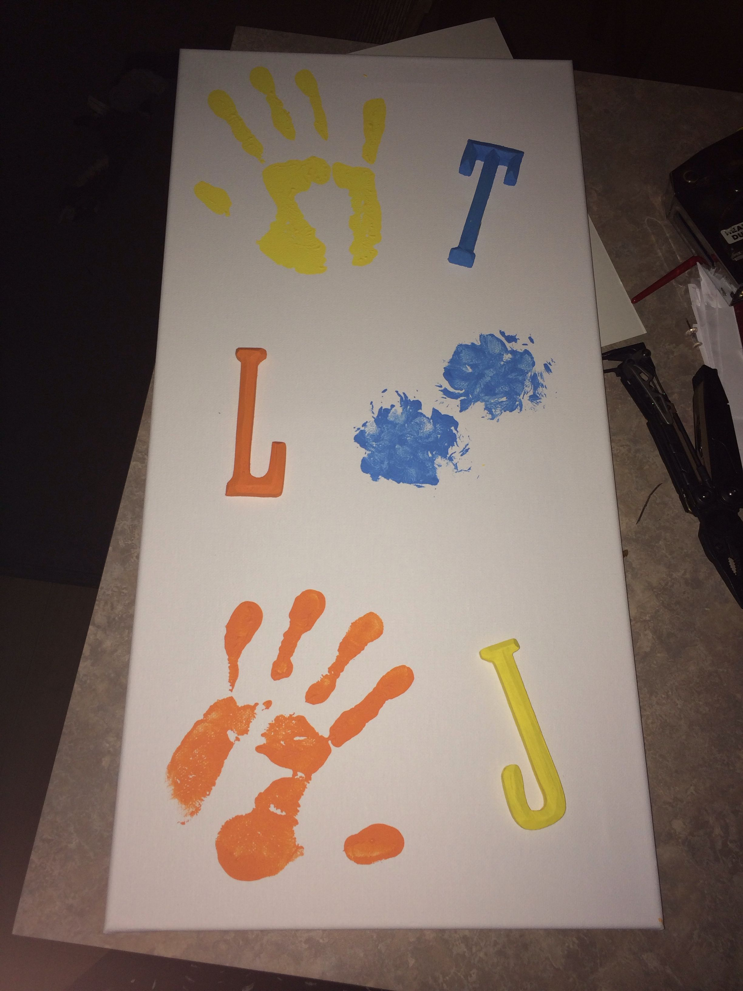 This is my hand and my husbands hand and our one year old puppy's paws. Made on canvas with acrylic paints. The wooden letters have been painted and glued to the canvas and symbolize our first initials.