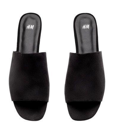 Sort. Et par slip-in sandaler. Innersåler og fôr i skinnimitasjon. Yttersåler i gummi.