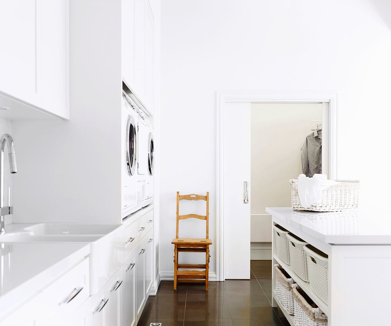 """With plenty of room to play with, this laundry – serving a large family – accommodates two washing machines, a double trough and a walk-in drying closet. Completely overhauled by Melbourne architecture and design firm [Canny](http://www.canny.com.au/?utm_campaign=supplier/ target=""""_blank""""), the room features a Stone Italiana-topped island for folding clothes, and wicker baskets for sorting them. Photo: Supplied by Canny"""