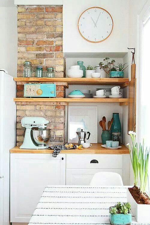 Parede de tijolos à vista na cozinha, atrás de estantes de madeira - estantes para cocina