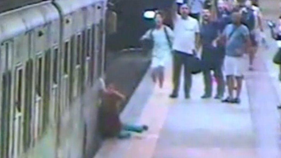 Woman on Rome metro dragged along platform by train https://tmbw.news/woman-on-rome-metro-dragged-along-platform-by-train  Footage of a woman being dragged along a platform by a train, after her bag got trapped in the door, has raised safety questions about Rome's metro.Natalya Garkovich, 43, was left in intensive care after sensors failed to register the strap and emergency breaks did not stop the train's advance.The footage also shows train driver Gianluca Tonelli eating his lunch before…