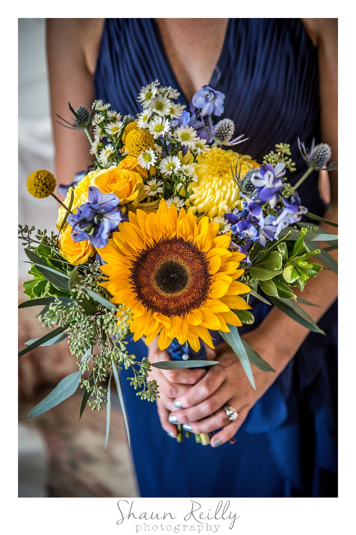 Sunflowers With Light Purple Flowers And A Navy Blue Bridesmaid