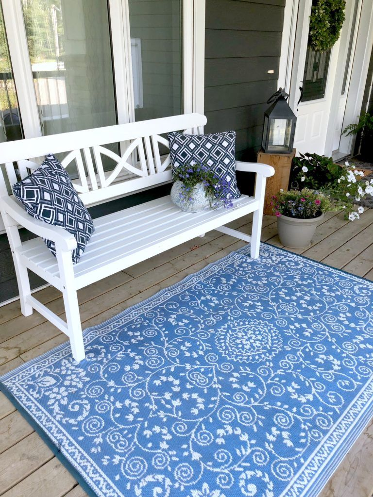 Farmhouse style front porch with white wood bench and blue