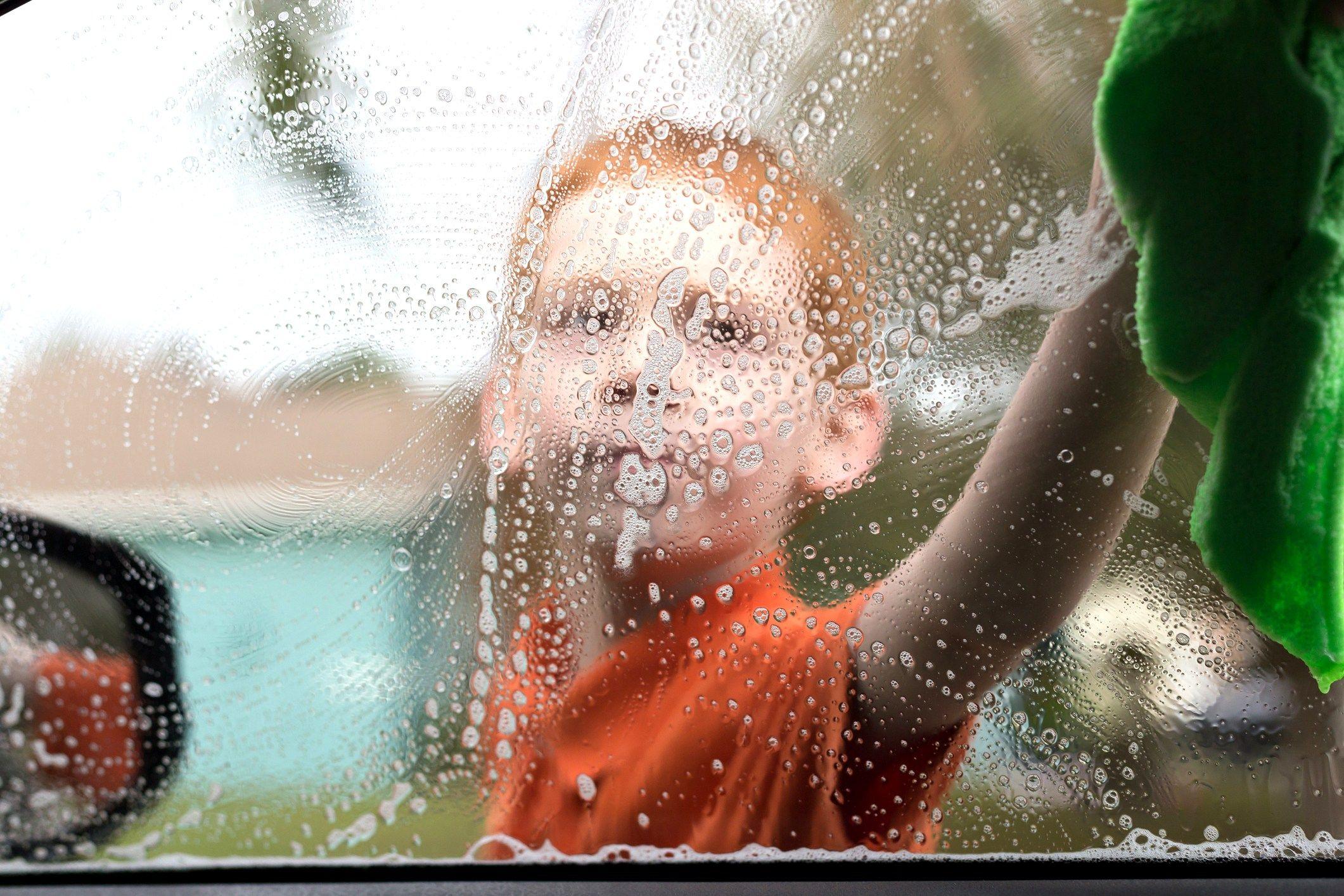 little boy washing a car window