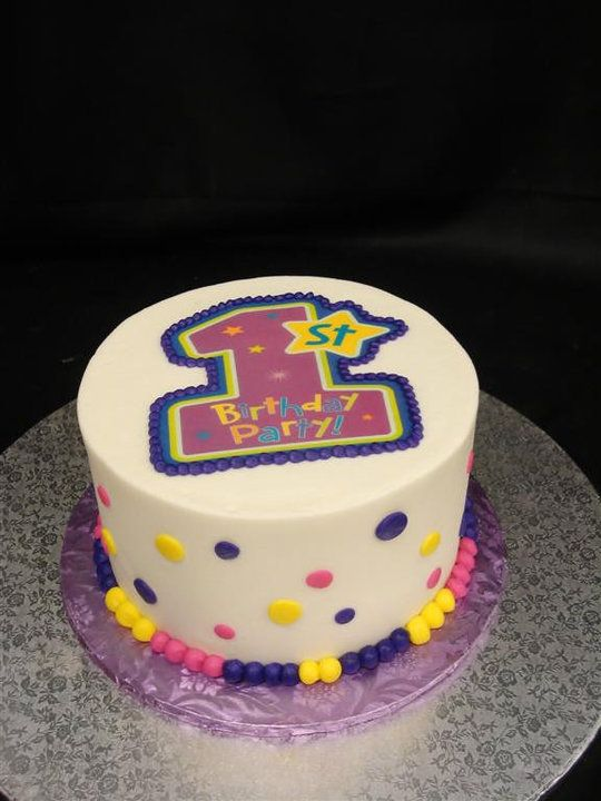 A White 1st Birthday Cake With Pink Purple And Yellow Polka Dots PartyFlavors