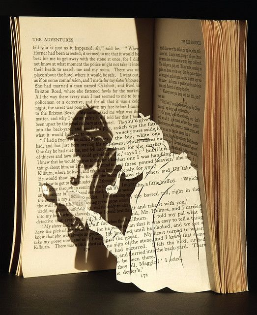 Sherlock Holmes paper cut with real magnifying glass and projector-produced shadow. By Rochelle Donald.