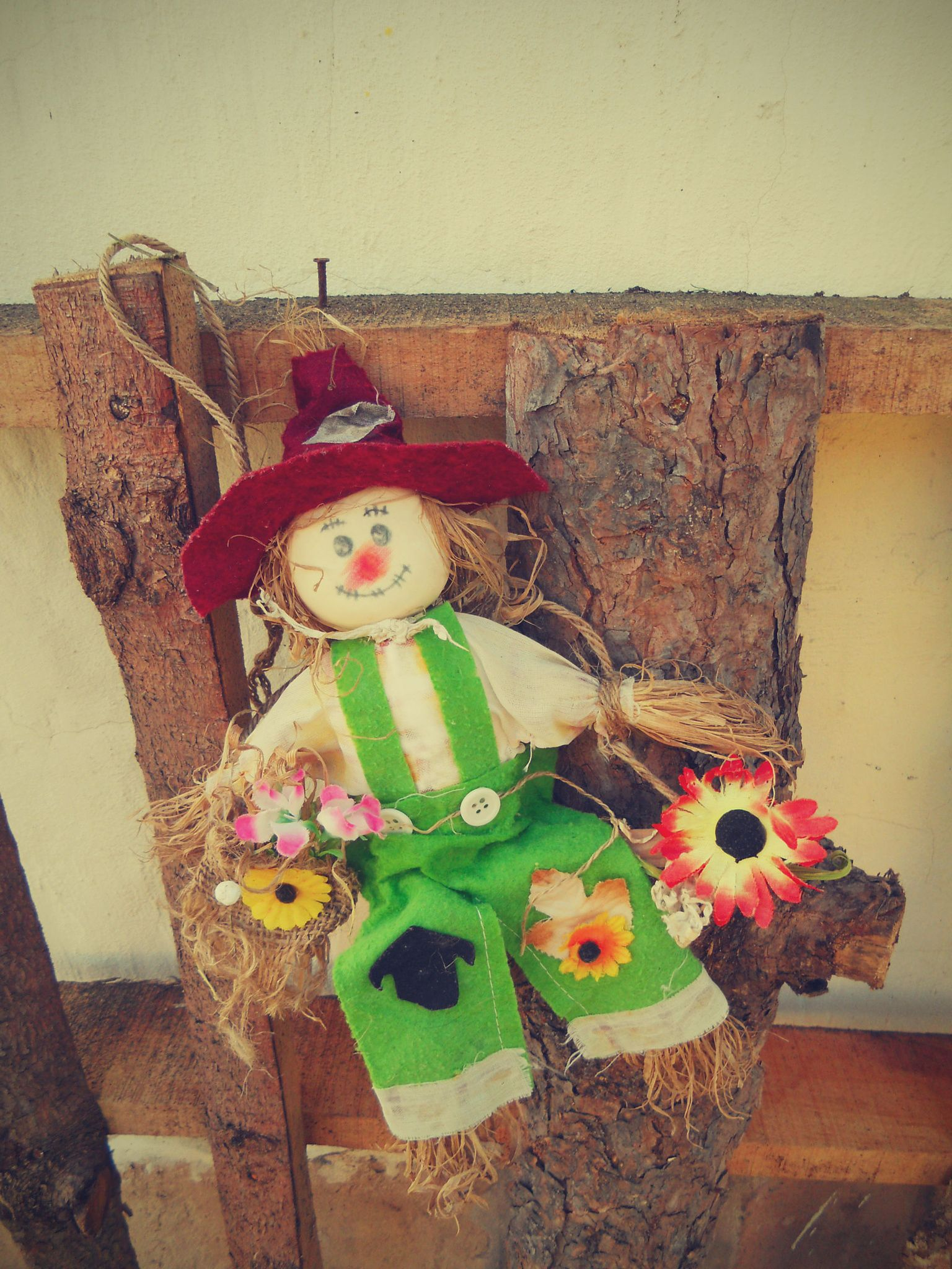 Cheerful Scarecrow hanging on wooden boards - Cheerful cute Scarecrow,  rag-doll hanging on wooden boards against the background yellow wall.
