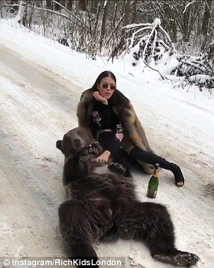 Woman in fur coat sparks outrage posing with BEAR and