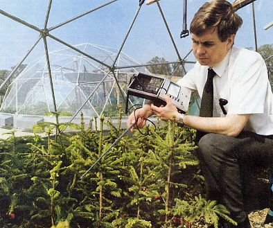 """Probe in hand an acid-rain researcher works inside a climate-controlled """"solar dome"""" greenhouse at the Central Electricity Research Laboratories at Leather-head"""